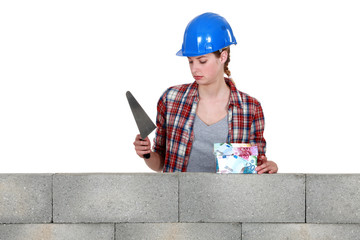 Female mason stood with trowel and house made from money