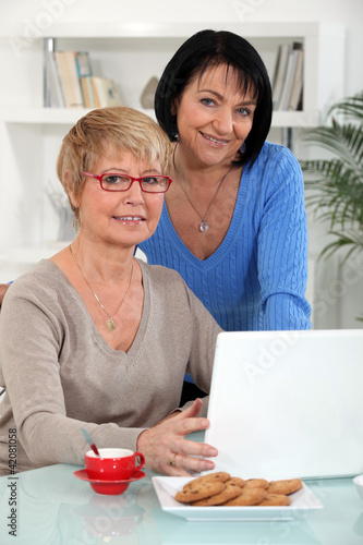 Two middle-aged women with laptop