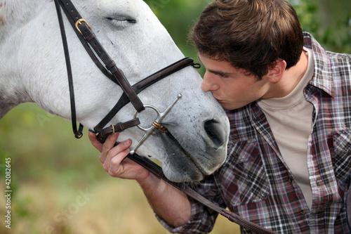 A man patting his horse