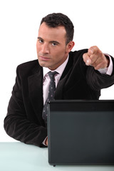 A businessman pointing a the camera.