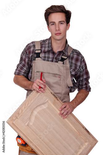 Carpenter holding cupboard door