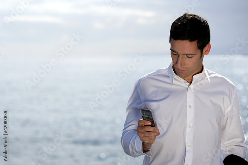 Man sending an SMS by the water's edge