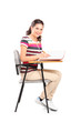 A schoolgirl sitting on a chair and writing down notes