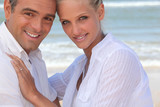 Couple wearing white clothing stood on a beach
