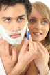 Young woman embracing her boyfriend while shaving