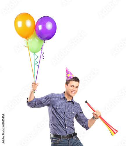 Portrait of a happy male holding balloons and a horn