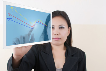 Business lady writing up graph on tablet screen.