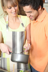 Young couple with a saucepan