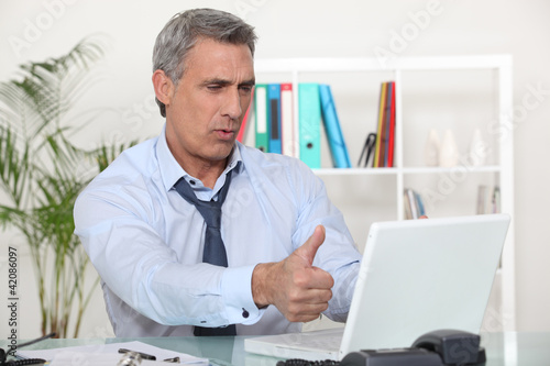 Middle-aged office worker giving thumbs-up