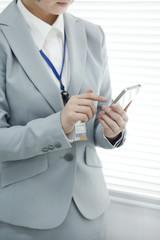 スマートフォンを操作する女ビジネスウーマン