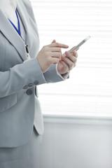 スマートフォンを操作するビジネスウーマン