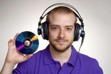 joven dj sujetando un cd y audífonos,escuchando música.