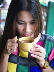 women drink coffee in park