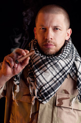 Soldier in combat uniform smoking cigar, over dark background