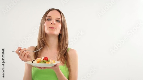 Beautiful young womaneating fruit salad; Full HD Photo JPEG