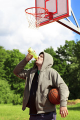Man holding basketball and drink from bottle of water