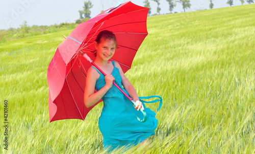 teenage girl with red umbrella in wheat field