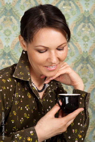 Beautiful Caucasian lady with a cup sitting