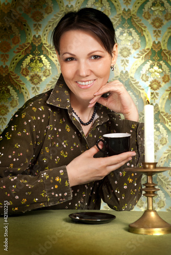 Beautiful Caucasian woman with a cup sitting
