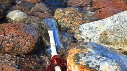 Flaschenpost zwischen Felsen und Wasser am Strand
