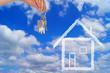 Hand mit Wohnungsschlüssel über blauem Himmel