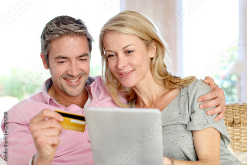 Couple sitting in sofa at home and doing online shopping