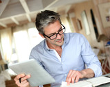 Fototapety Handsome businessman with eyeglasses working from home