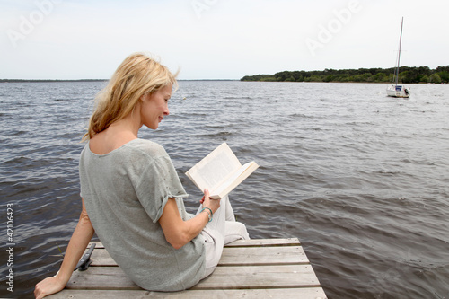 Woman reading book sitting on lake boardwalk