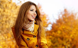 Fototapety Beautiful elegant woman standing in a park in autumn