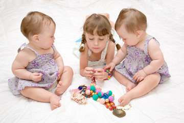 preschooler and baby twins playing with colorful beads