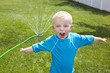 Little Boy playing in the Backyard sprinklers