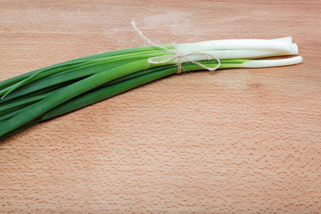 Bunch of fresh green onions on a wooden table.