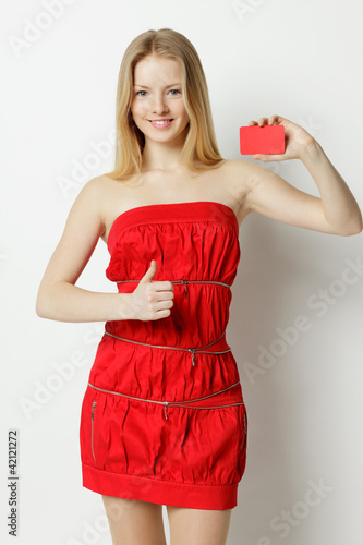 Woman holding blank credit card, showing thumb up sign