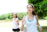 Fototapety Beautiful young women running in park. Portrait of asian.