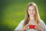 Young beautiful girl holding a blank credit card outdoors