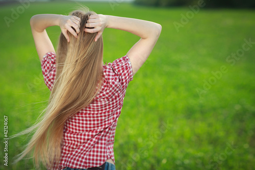Back of attractive young woman relaxing with hands behind head
