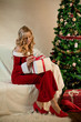Beautiful woman in santa costume next to Christmas Tree