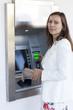 Frau hebt Geld am Geldautomaten ab