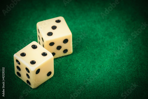 Two dice on a green gaming table with space for text