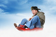 Funny man in earflaps, on a sled in the snow