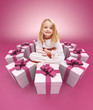 Happy little girl surrounded by gifts pink
