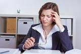 Geschäftsfrau mit Kopfschmerzen im Büro