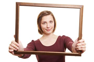 Frau schaut durch leeren Rahmen