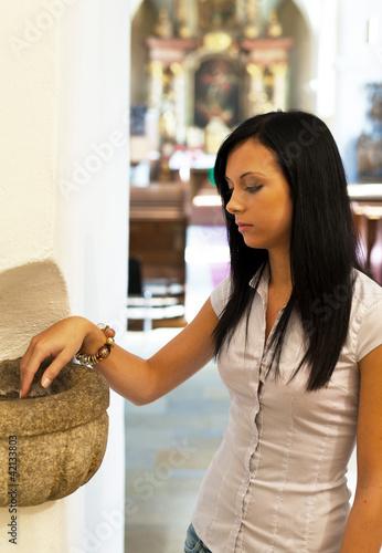 Frau in einer Kirche mit Weihwasser