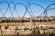 The Old City of Jerusalem seen through coils of razor wire