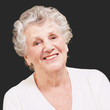 senior woman smiling against a black background