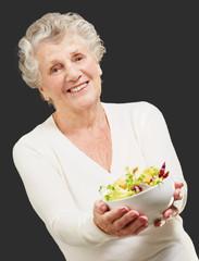 portrait of senior woman showing a fresh salad over black backgr