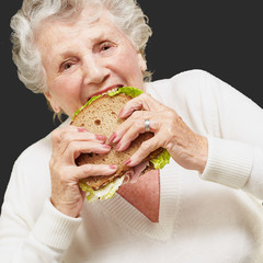 portrait of senior woman eating vegetal sandwich over black back