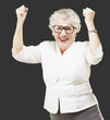 portrait of a cheerful senior woman gesturing victory over black