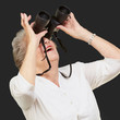 portrait of senior woman looking through a binoculars over black